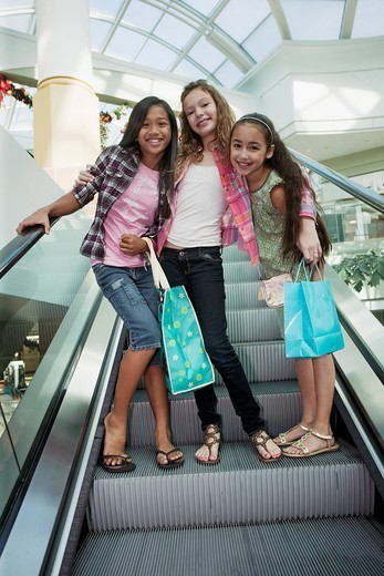 Friends carrying shopping bags on shopping mall escalator : Stock Photo