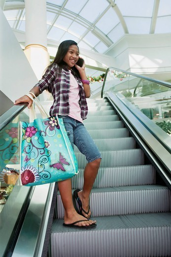 Mixed race girl talking on cell phone on shopping mall escalator : Stock Photo