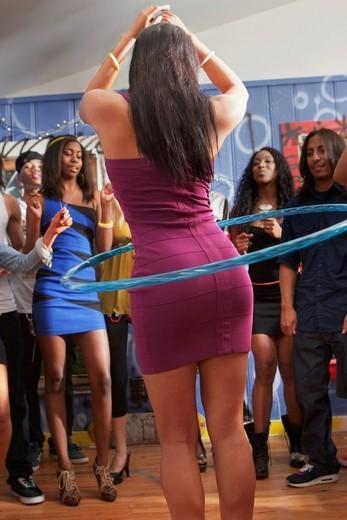 Friends watching woman using hula hoop at party : Stock Photo