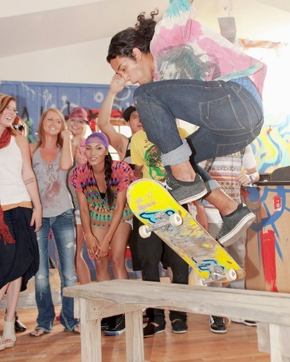 Friends watching man on skateboard at party : Stock Photo