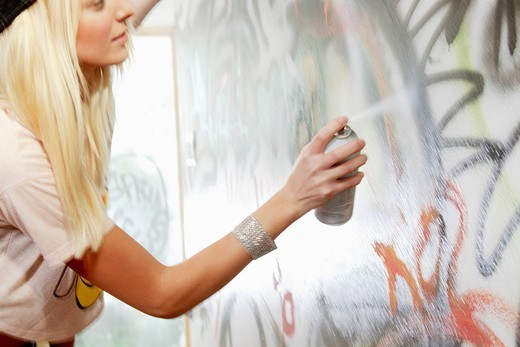 Caucasian woman tagging wall with graffiti : Stock Photo