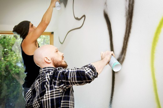 Men tagging wall with graffiti : Stock Photo