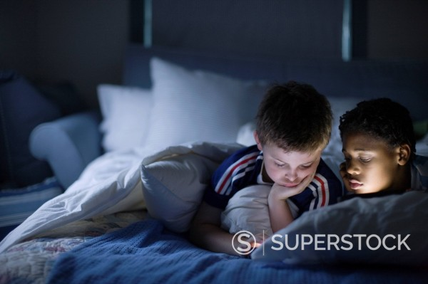 Stock Photo: 1589-163717 Boys looking at video game at night