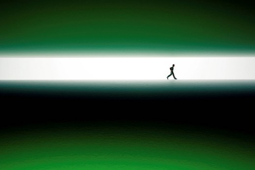 Silhouette of man walking across green surface : Stock Photo