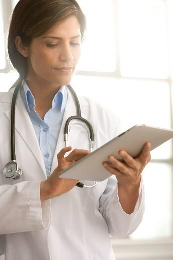 Hispanic doctor using digital tablet : Stock Photo