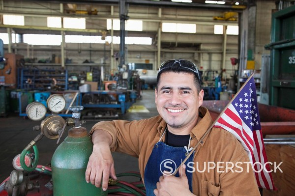 Stock Photo: 1589-164041 Hispanic worker standing in factory with American flag