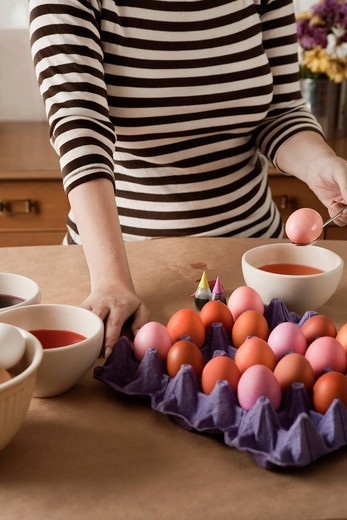 Woman dying Easter eggs : Stock Photo