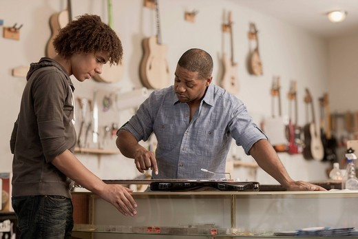 Father and son in music workshop : Stock Photo