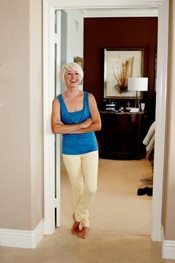 Caucasian woman leaning on wall with arms crossed : Stock Photo