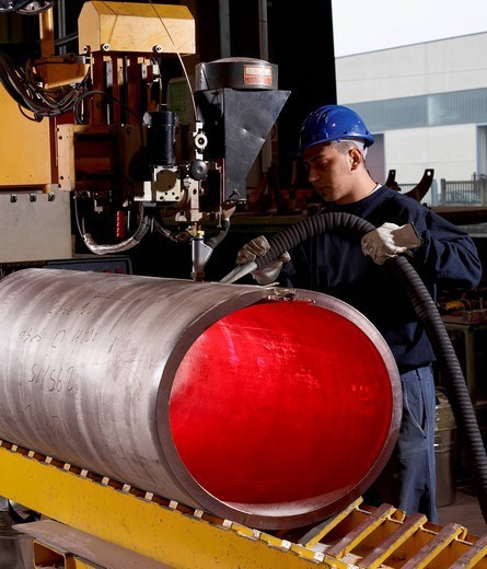 Caucasian worker working on steel pipe in factory : Stock Photo