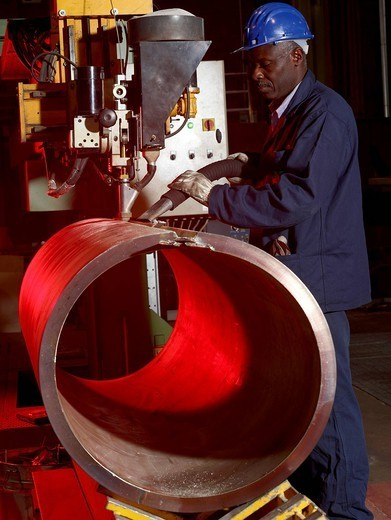 Worker working on steel pipe in factory : Stock Photo