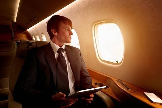 Caucasian businessman using digital tablet on private jet : Stock Photo