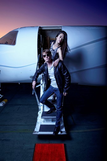 Couple waking down steps of private jet : Stock Photo