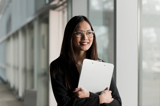 Asian businesswoman holding clipboard : Stock Photo