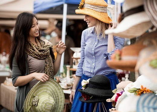 Friends shopping for hats at flea market : Stock Photo