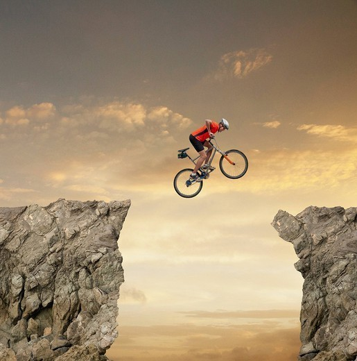 Mixed race bicyclist jumping over canyon : Stock Photo