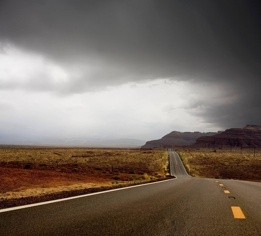 Remote highway and cliff with storm above : Stock Photo