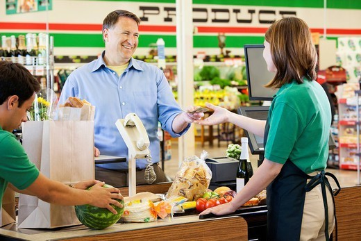 Customer paying cashier in grocery store : Stock Photo