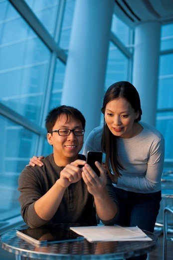 Asian couple looking at cell phone : Stock Photo