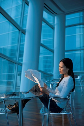 Asian businesswoman looking at paperwork : Stock Photo