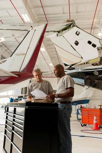 Men working in airplane hangar : Stock Photo