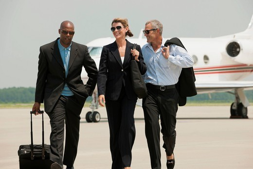 Business people walking on airport tarmac : Stock Photo