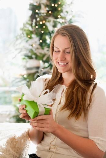 Caucasian woman holding Christmas gift : Stock Photo