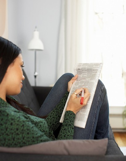 Woman reading classified ads in newspaper : Stock Photo