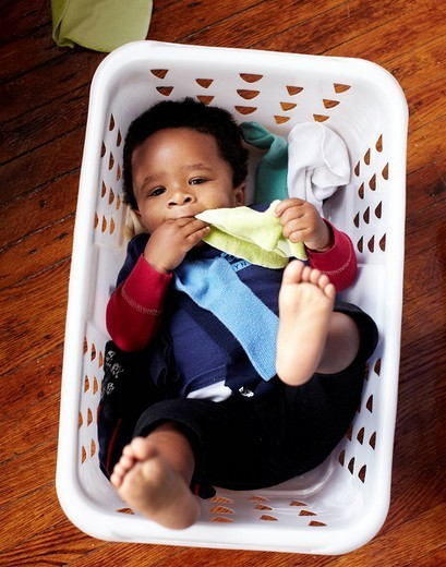 African American baby laying in laundry basket : Stock Photo
