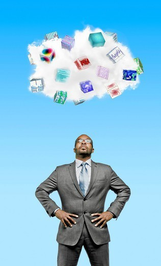 African American businessman looking at cloud containing cubes with pictures : Stock Photo