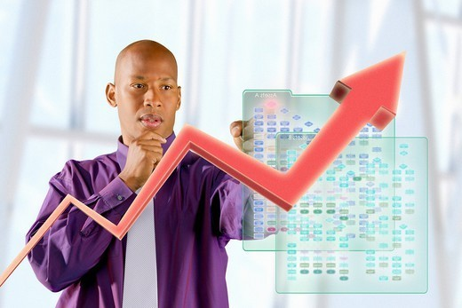 Black businessman looking at line graph : Stock Photo