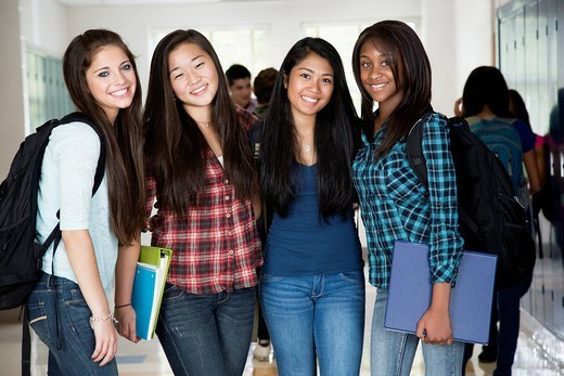 High school friends standing in corridor together : Stock Photo