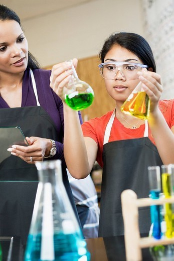 Teacher and student working with chemicals in classroom : Stock Photo