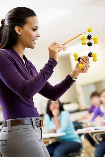 Teacher explaining chemistry model to classroom : Stock Photo