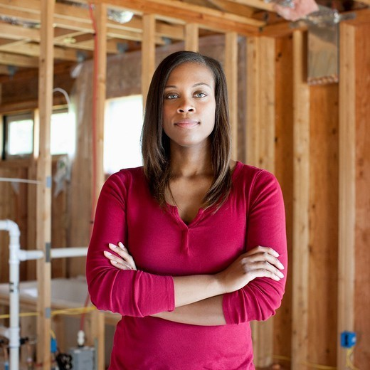 Black woman standing in unfinished room : Stock Photo