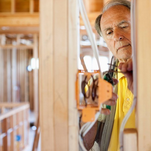 Caucasian electrician working on wiring in unfinished room : Stock Photo