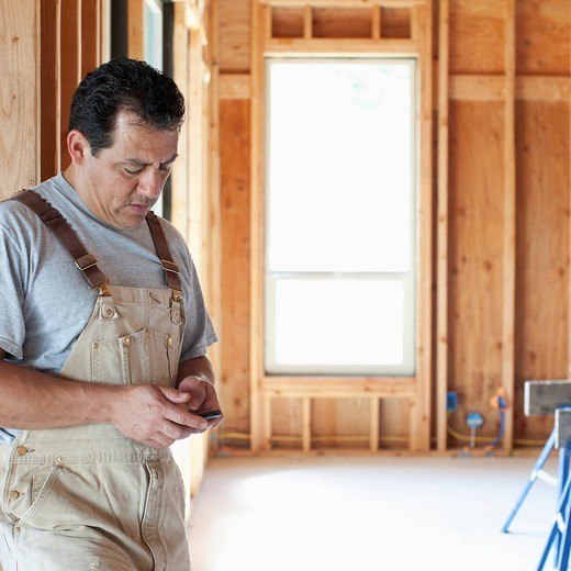Hispanic construction worker text messaging on cell phone in unfinished room : Stock Photo