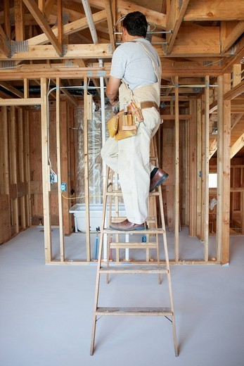 Hispanic construction worker on ladder in unfinished room : Stock Photo