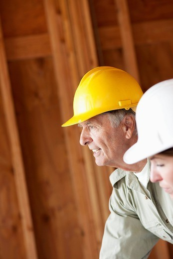 Caucasian construction workers in unfinished room : Stock Photo