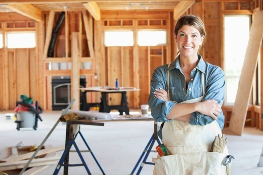 Caucasian construction worker standing in unfinished room : Stock Photo