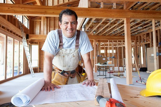 Hispanic construction worker looking at blueprints in unfinished room : Stock Photo