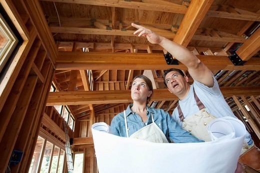 Construction workers looking at blueprints in unfinished room : Stock Photo