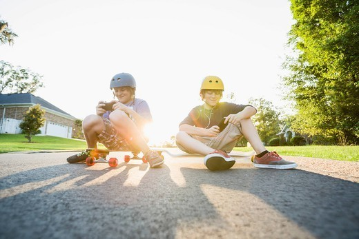 Caucasian boys sitting on skateboards and using cell phones : Stock Photo