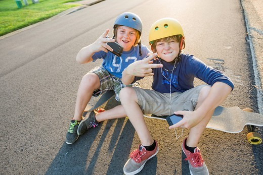 Caucasian boys sitting on skateboards and making gestures : Stock Photo