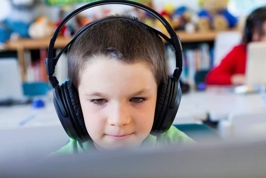 Caucasian student in headphones using laptop in classroom : Stock Photo