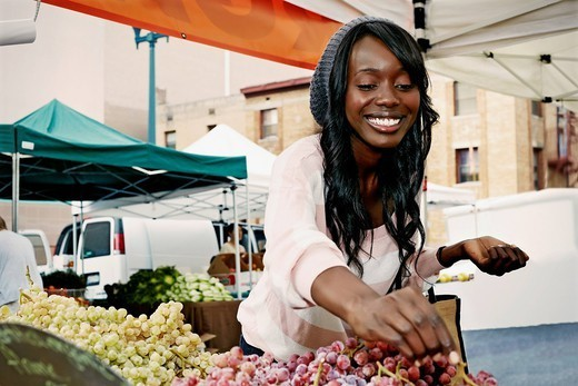 African American woman buying grapes : Stock Photo