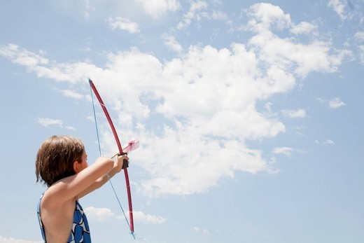Caucasian girl aiming bow and arrow : Stock Photo