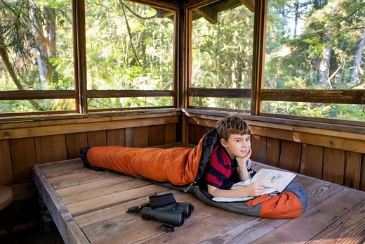 Caucasian boy reading in sleeping bag : Stock Photo