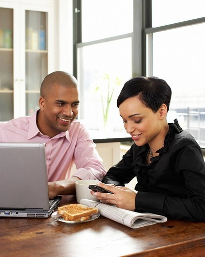 Couple eating breakfast and using laptop and cell phone : Stock Photo