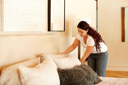 Hispanic woman making bed : Stock Photo